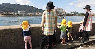 保育士と海辺を散歩している子供たち