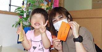 笹の葉に飾る短冊を手に持つ親子