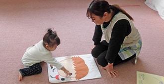 福笑いをする子供と保育士